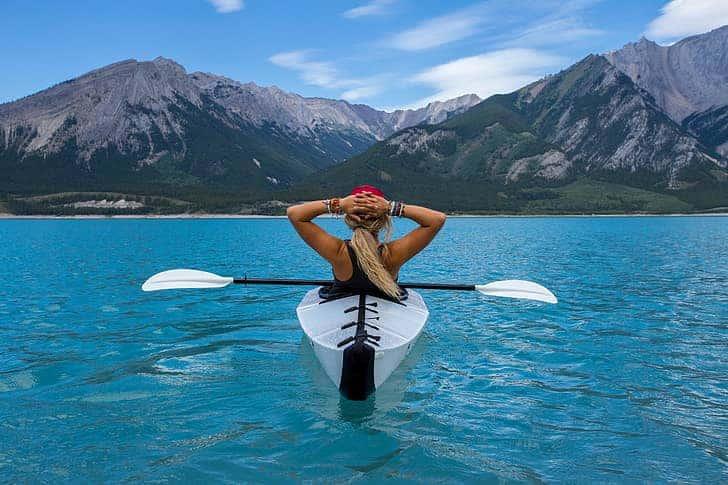 girl kayaking with white paddle