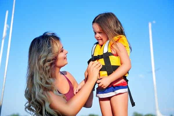 Mother putting life vest on her daughter